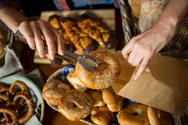 Seção intermediária da equipe embalando donut em saco de papel no balcão Foto Premium