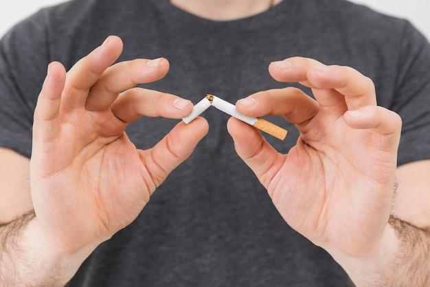Seção intermediária da mão de um homem quebrando o cigarro Foto gratuita