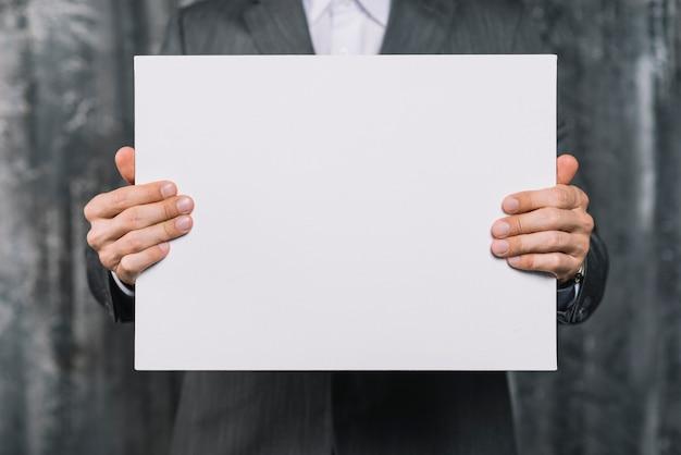 Seção intermediária de um empresário mostrando o cartaz branco em branco Foto gratuita