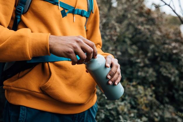 Seção intermediária de um homem abrindo a tampa da garrafa de água Foto gratuita