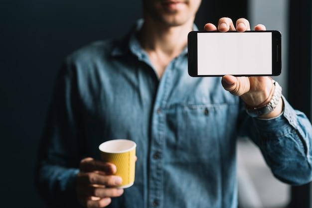 Seção intermediária de um homem segurando o copo de café descartável, mostrando a tela do celular Foto gratuita