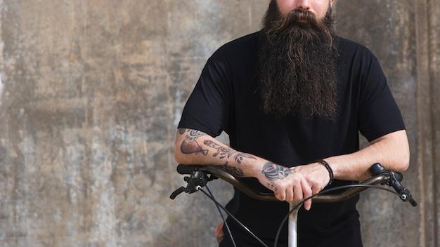 Seção intermediária de um homem sentado na bicicleta contra o pano de fundo concreto Foto gratuita