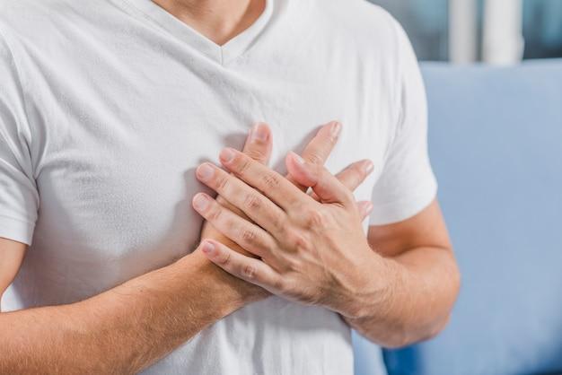 Seção intermediária de um homem tocando seu peito com as mãos Foto gratuita