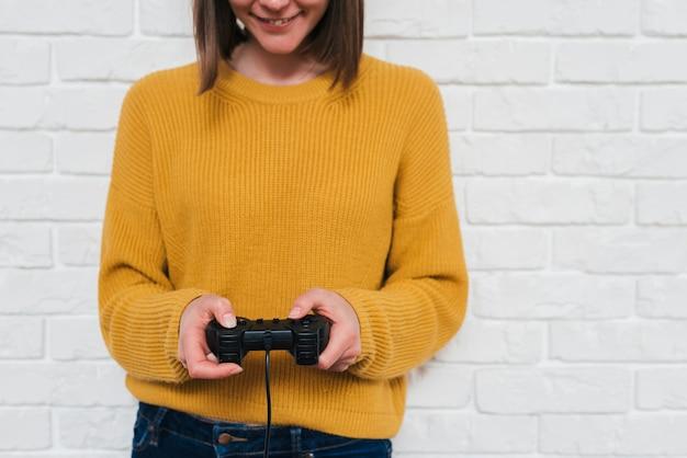 Seção intermediária de uma jovem mulher jogando videogame com joystick Foto gratuita