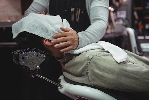 Seção intermediária do barbeiro, enxugando o rosto dos clientes com uma toalha quente Foto gratuita