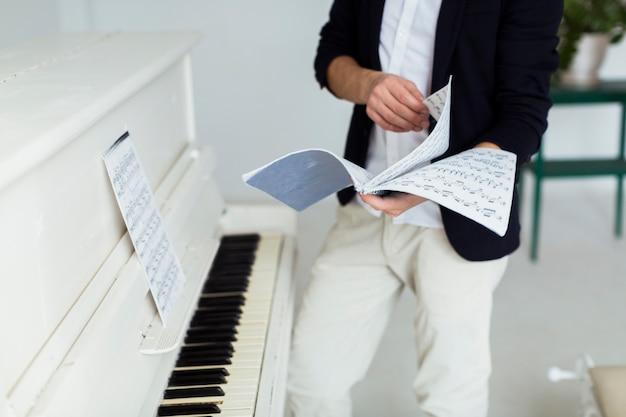 Seção intermediária do homem virando as páginas de folhas musicais perto do piano de cauda Foto gratuita