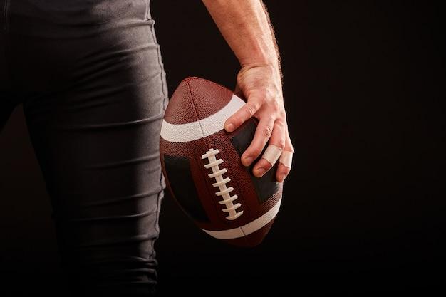 Seção intermediária do jogador de futebol americano com bola contra preto, copie o espaço, vista traseira Foto Premium