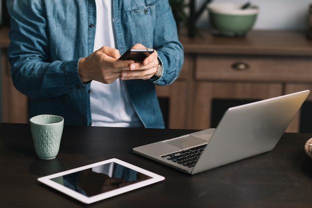 Seção intermediária do jovem usando smartphone com laptop; tablet digital e caneca de café no balcão da cozinha Foto gratuita