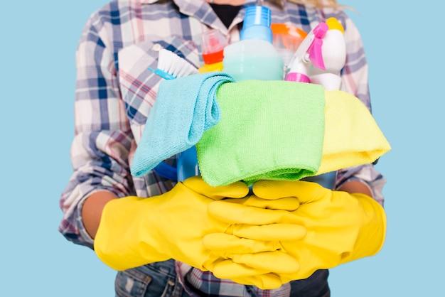 Seção intermediária do limpador segurando balde com produtos de limpeza usando luvas amarelas Foto gratuita