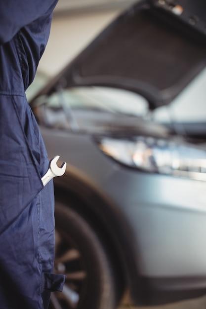 Seção intermediária do mecânico com uma chave inglesa no bolso Foto gratuita