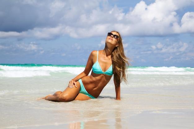 Seção meados de da jovem mulher no biquini azul que sunbathing na areia branca. menina da moda de bronzeamento na praia tropical Foto Premium