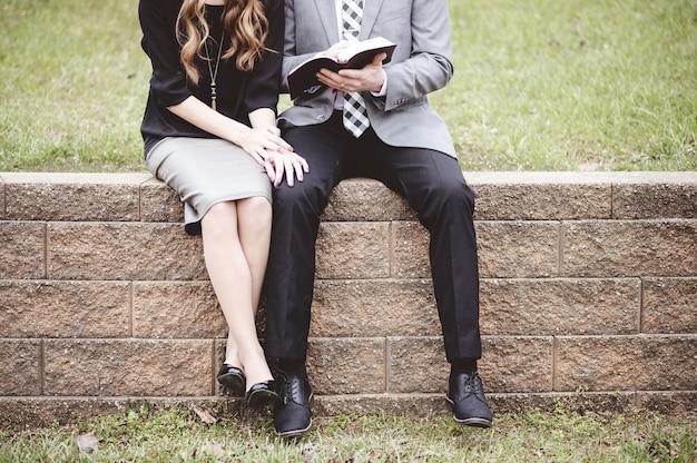 Seção mediana de um casal sentado em blocos e lendo um livro com amor Foto gratuita