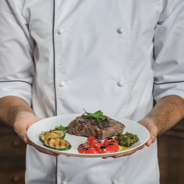 Seção mid, de, macho, cozinheiro, segurando, preparado, bife carne, com, legumes Foto gratuita