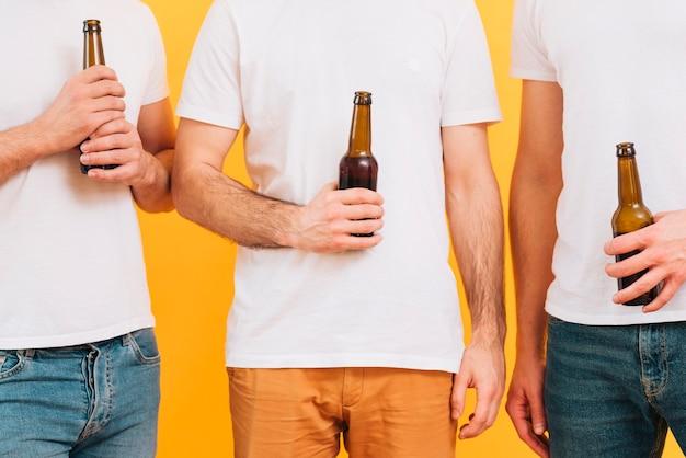 Seção mid, de, três homens, em, branca, t-shirt, segurando, garrafa cerveja Foto gratuita