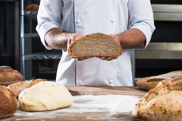 Seção mid, de, um, macho, padeiro, segurando pão Foto gratuita