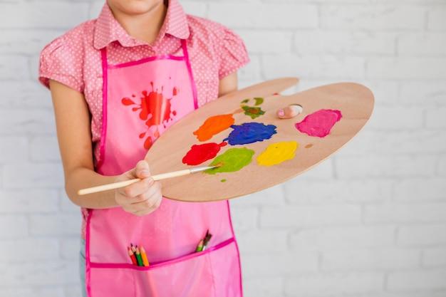 Seção mid, de, um, menina, desgastar, cor-de-rosa, avental, misturando, a, pintura, ligado, paleta, com, pincel Foto gratuita