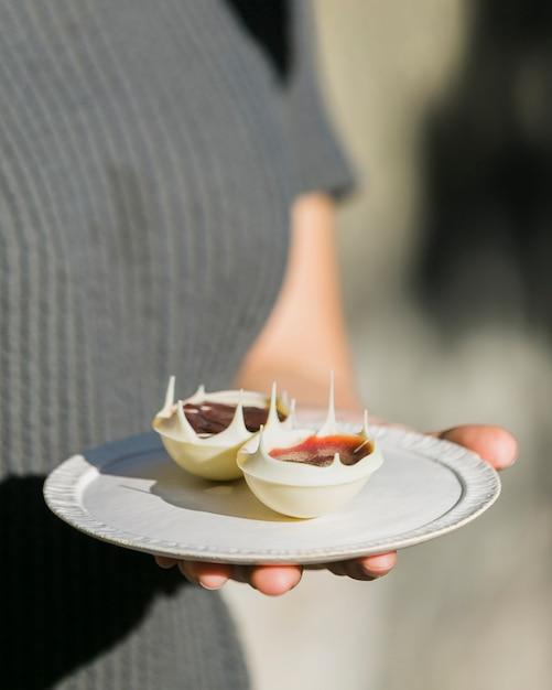 Seção mid, de, um, mulher segura prato, com, branca, sobremesa chocolate Foto gratuita