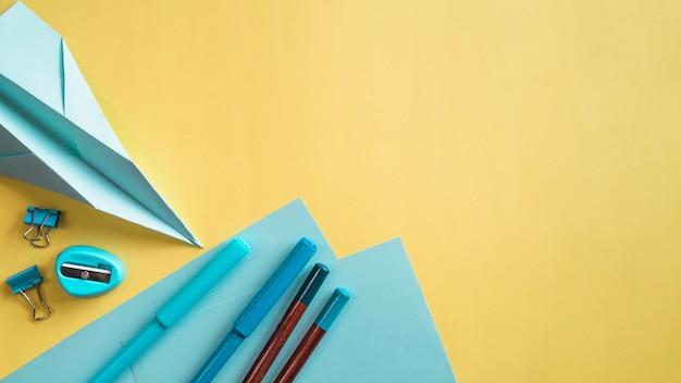 Secretária criativa com artigos de papelaria na parede amarela Foto gratuita