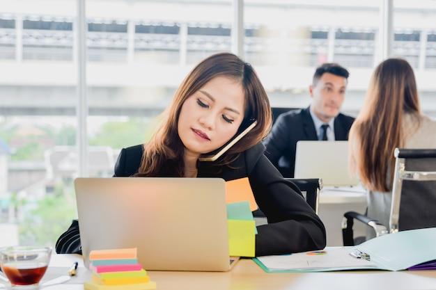 Secretário do conceito do negócio que fala no telefone no escritório, mulher de negócio no trabalho no escritório Foto Premium