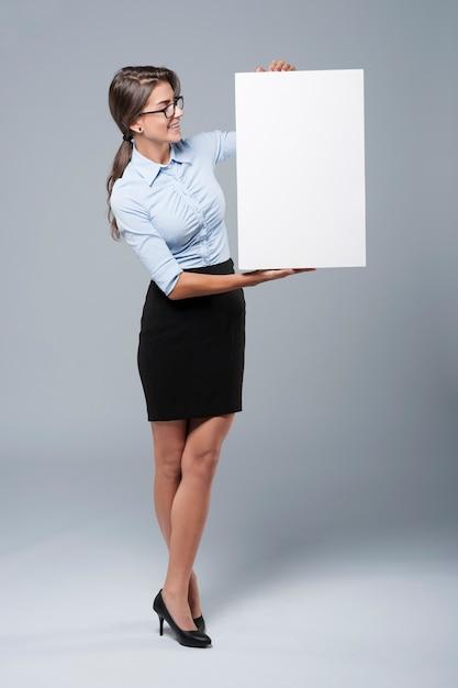 Secretário segurando um cartaz vertical vazio Foto gratuita