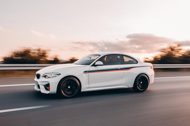Sedan branco do esporte com ajuste colorido na estrada. Foto gratuita