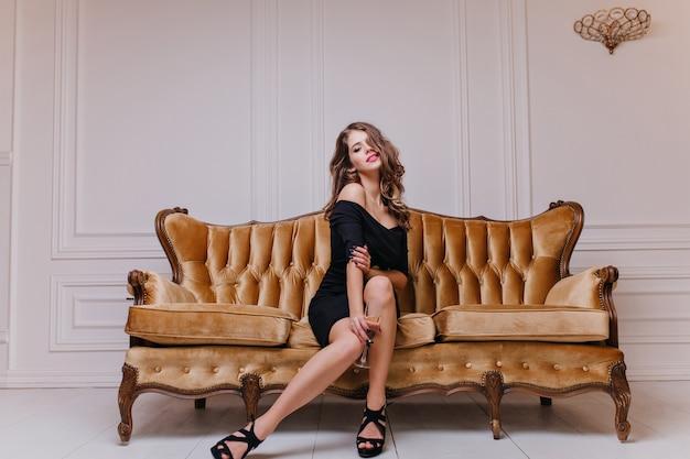 Sedutora e misteriosa aristocrata europeia com cachos longos, batom vermelho e elegante vestido preto posando no sofá real em uma sala iluminada Foto gratuita