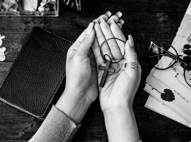 Segurando a cruz nas mãos com fidelidade Foto gratuita