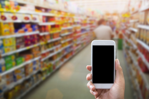 Segurando o telefone inteligente isolado sobre o branco, maquete Foto Premium