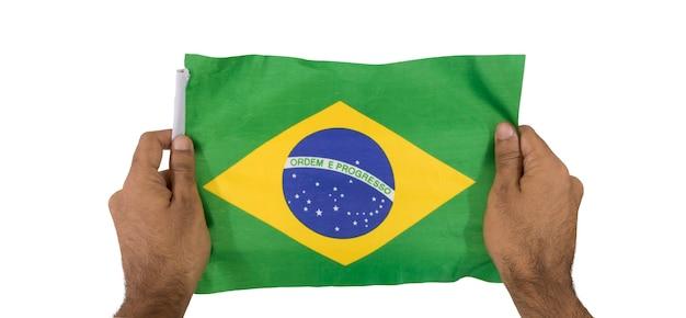 Segurando uma bandeira brasileira isolada no fundo branco. Foto Premium