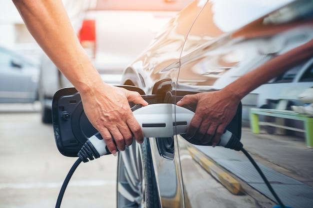 Segurar a mão de carregar moderna bateria de carro elétrico na rua, que é o futuro do automóvel, close-up da fonte de alimentação conectada a um carro elétrico sendo cobrado por híbrido Foto Premium