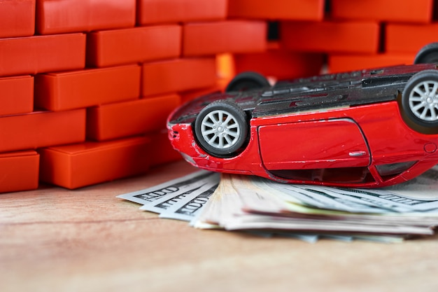 Seguro de vida em um conceito de acidente de carro. notas de carro e dólar quebradas Foto Premium