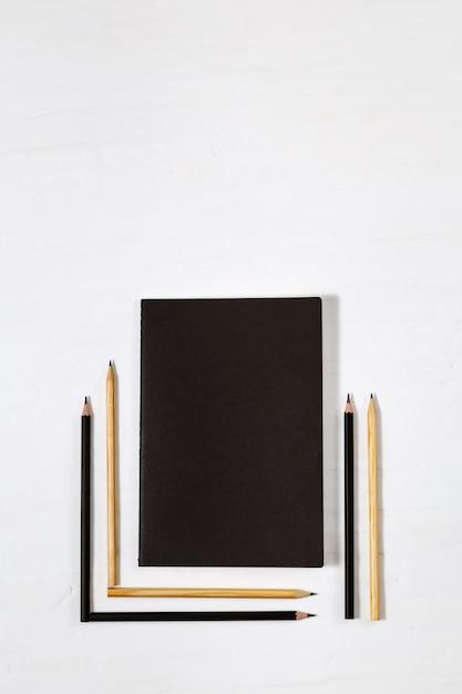 Seis lápis de madeira e livro preto fechado Foto Premium