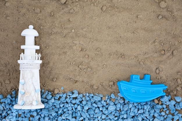 Seixos azuis leigos planos com farol e barco na areia Foto gratuita