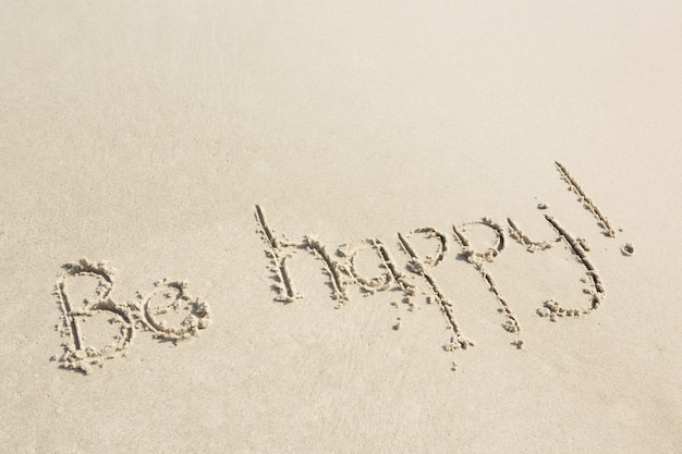 Seja feliz escrito na areia Foto gratuita