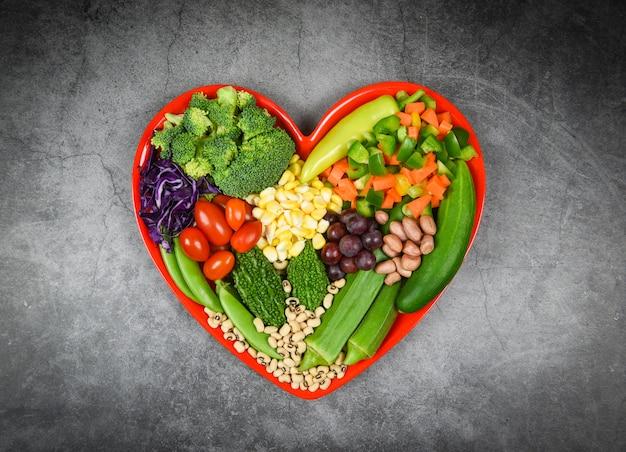 Seleção de alimentos saudáveis alimentação limpa para a vida do coração colesterol dieta saúde salada fresca de frutas e legumes verdes misturados vários grãos de nozes feijão no prato de coração vermelho para comida saudável cozinheiro vegan Foto Premium
