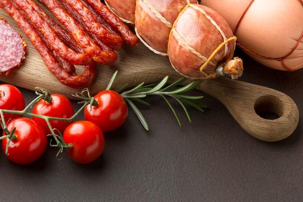 Seleção de close-up de carne fresca com tomate em cima da mesa Foto gratuita