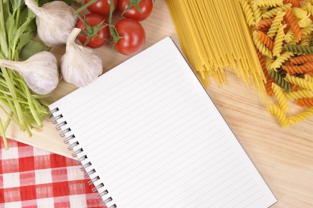 Seleção de macarrão com livro de receitas em branco Foto Premium