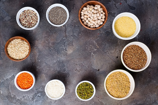 Seleção de superalimentos e cereais em taças em fundo cinza de concreto Foto Premium
