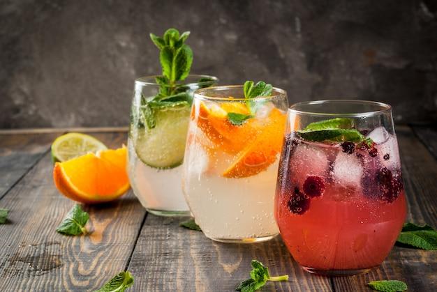 Seleção de três tipos de gin tônico: com amoras com laranja com limão e folhas de hortelã. em copos em um fundo de madeira rústico. Foto Premium