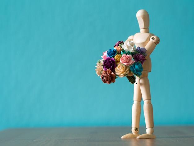 Selecione o foco do boneco de madeira. o boneco de madeira mantém flor e em pé sobre a mesa de madeira. Foto Premium