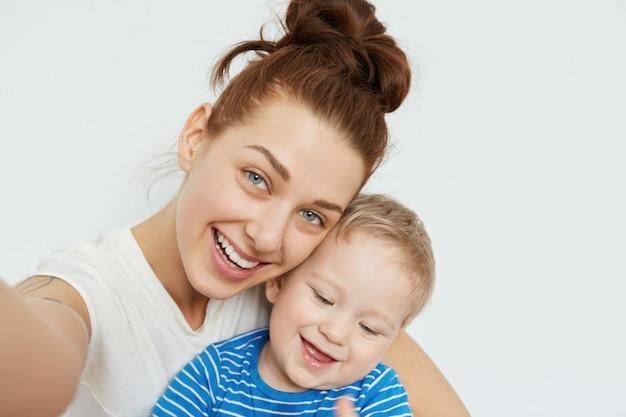 Selfie de família positivo com a jovem mamãe e criança desdentada sorrindo juntos na parede branca. o estado de espírito lúdico e o humor feliz de uma mulher atraente tornam esta foto fabulosa e comovente. Foto gratuita