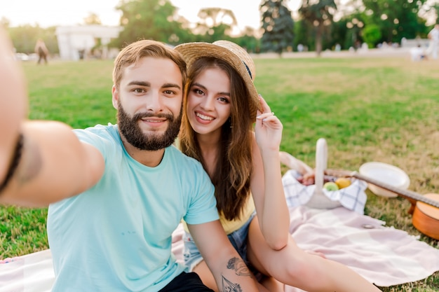 Selfie do jovem casal no piquenique no parque com cesta de frutas Foto Premium