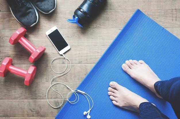 Selfie of feet yoga woman, smartphone, equipamentos esportivos e sapatos esportivos no chão de madeira Foto Premium