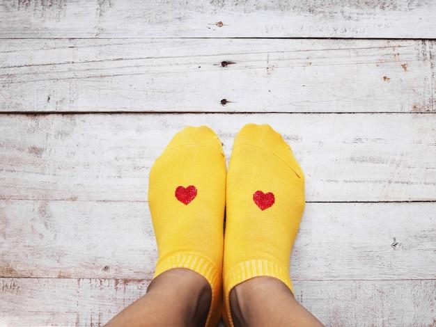 Selfie pés vestindo meias amarelas com forma de coração vermelho na madeira Foto Premium
