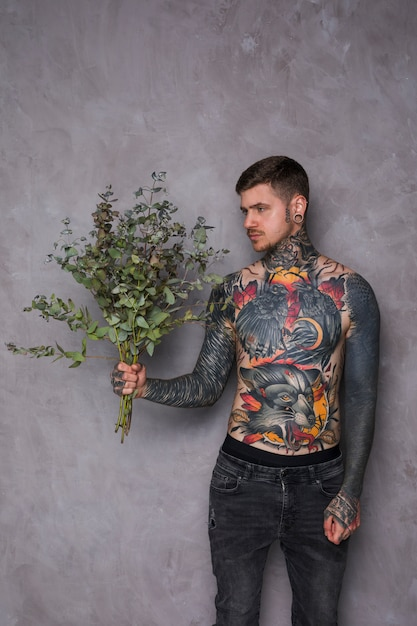 Sem camisa tatuada jovem em seu corpo e piercing em seus ouvidos e nariz, olhando para a câmera Foto gratuita