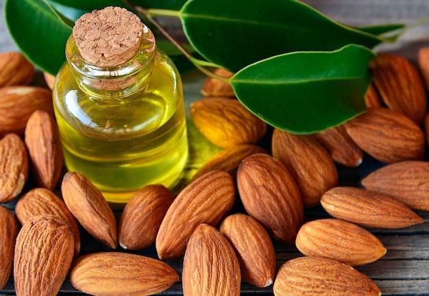 Semente de amêndoas e óleo de amêndoa no fundo de madeira velho para uma alimentação saudável, beleza e spa. foco seletivo. Foto Premium