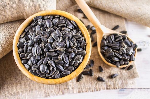 Semente de girassol fresca. sementes de girassol descascadas na bacia de madeira. Foto Premium