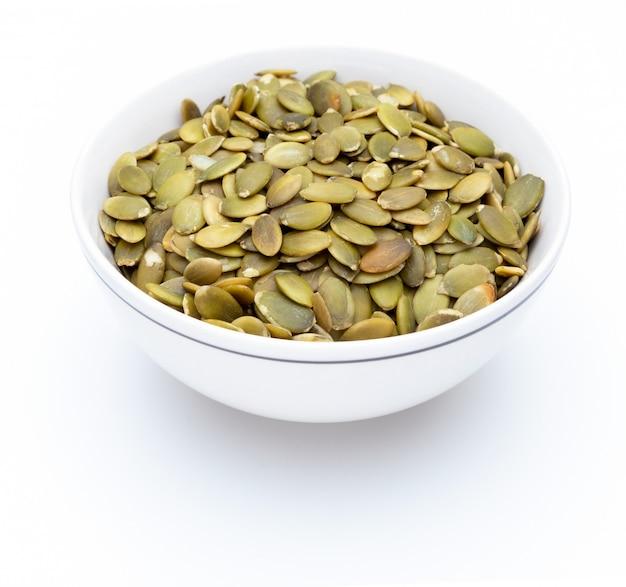 Sementes de abóbora (sementes descascadas) em tigela branca (coleção de nozes diversas). isolado Foto Premium