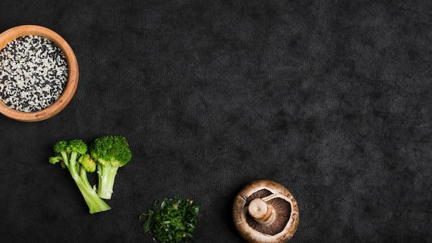 Sementes de gergelim; brócolis; cogumelo; cebola picada no pano de fundo preto textura Foto gratuita