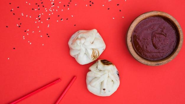 Sementes de gergelim; pauzinhos; bolinhos e molhos em tigela de madeira no pano de fundo vermelho Foto gratuita